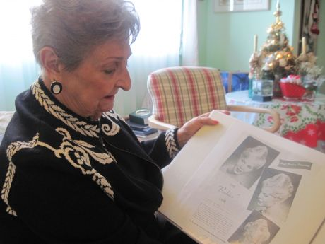 Margaret Vinci Heldt looks at a magazine clipping of the beehive hairstyle.